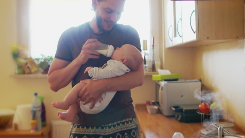 Handsome man is feeding the child from the bottle and calms him down. Baby food, artificial feeding of babies, caring for babies, pediatric physiology, pediatrics. Father's Day | Shutterstock HD Video #1014111833