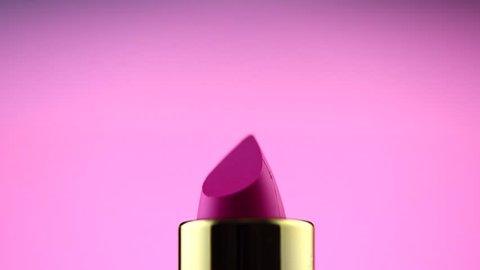 Lipstick. Fashion Pink bright Lipstick rotated over Pink background. Lipsticks tint, Professional Makeup and Beauty. Beautiful Make-up concept. Lipgloss closeup. UHD 4K video
