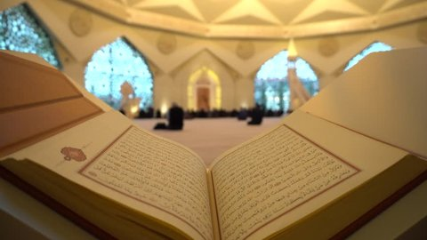 A Man Is Reading Quran Or Koran On The Reading Desk In A Mosque.