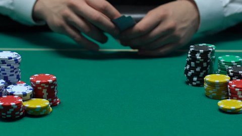 Player hand throwing pair of aces on table, win combination, poker bet, success