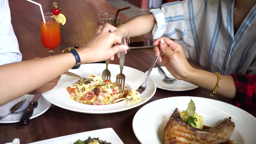 Close up of people taking and sharing a portion of spaghetti together. Friends grabbing food quickly