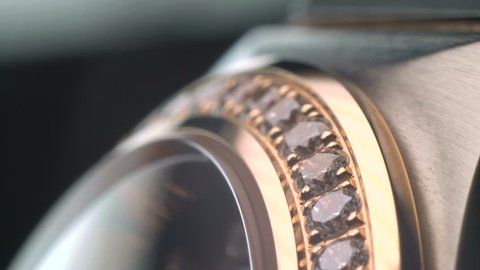 Luxury expensive fashion gold watches with sapphires and diamons.Arrows ticking. Close up 4k macro shot.