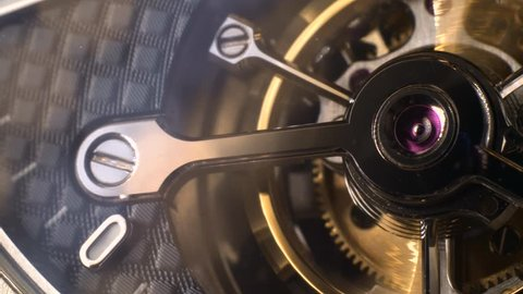 Mechanism of a watch with jewels. Open clockwork and fragments of shiny gears. Close up 4k macro shot. Time and work concept.