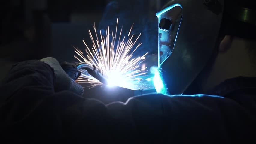 Industrial Worker labourer at the factory welding steel structure. Clip. Man welding metal