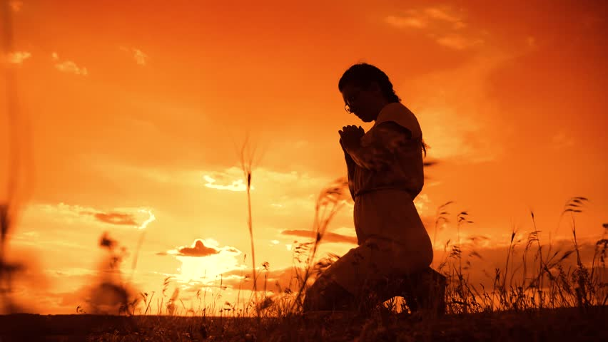 the girl prays. Girl folded her hands in prayer silhouette at sunset. slow motion video. Girl folded her hands in prayer pray to God. girl praying asks forgiveness for sins of repentance. concept