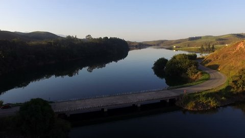 Aerial Drone Footage View: Flight over a damp and a bridge surrounded by mountains with a blue sky in the soft light of the sunset. South America, Serra da Bocaina National Park, Brazil.