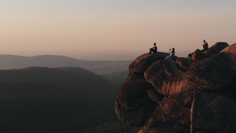 Epic drone shot of friends enjoy the sunset sitting on top of a high mountain in the Siberian Stolby nature reserve.