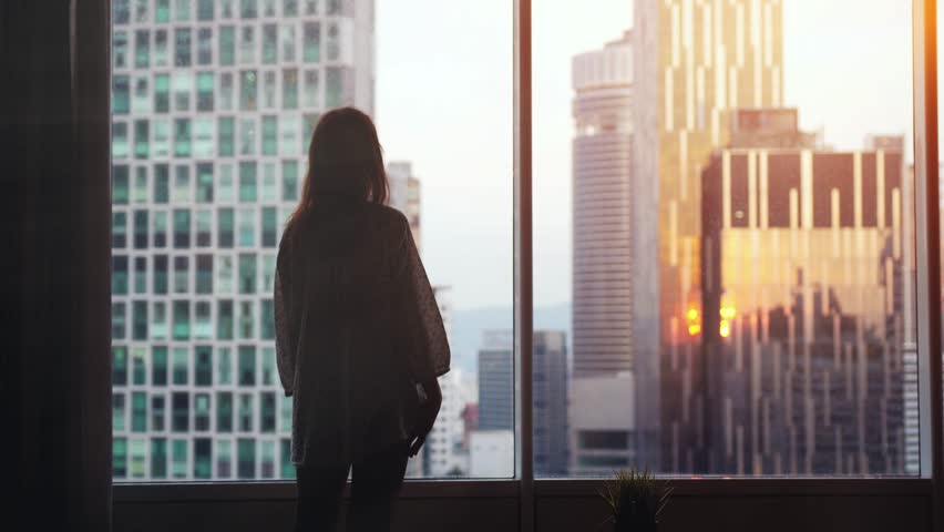 Young pensive woman stands by the big window looking out her apartment on the city buildings during sunset. slow motion. 3840x2160. #1014260393