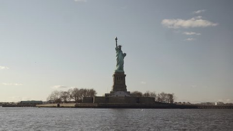Semi wide shot of Statue of Liberty filmed in the sunset from the river in New York, United States of America