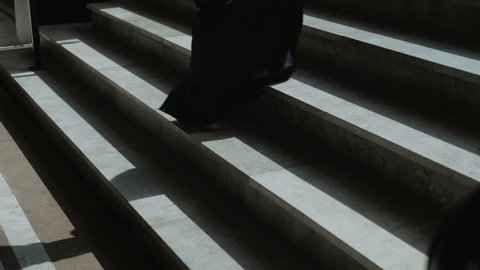 Women's legs without shoes in an elegant black dress Climbing the stairs. Slow motion