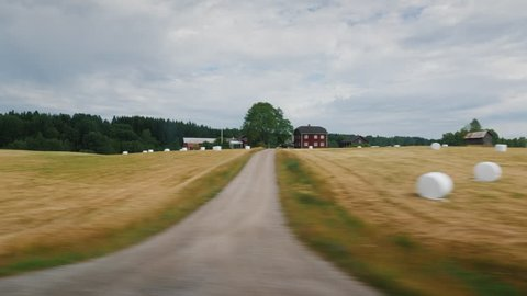 View from the window on the agricultural land of Norway, where mowing hay and lying in haystacks. Beautiful and clean corner of the planet