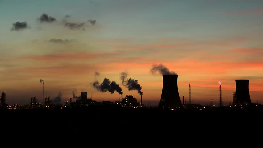 Cooling towers at oil refinery with steam. Sun setting sky time lapse