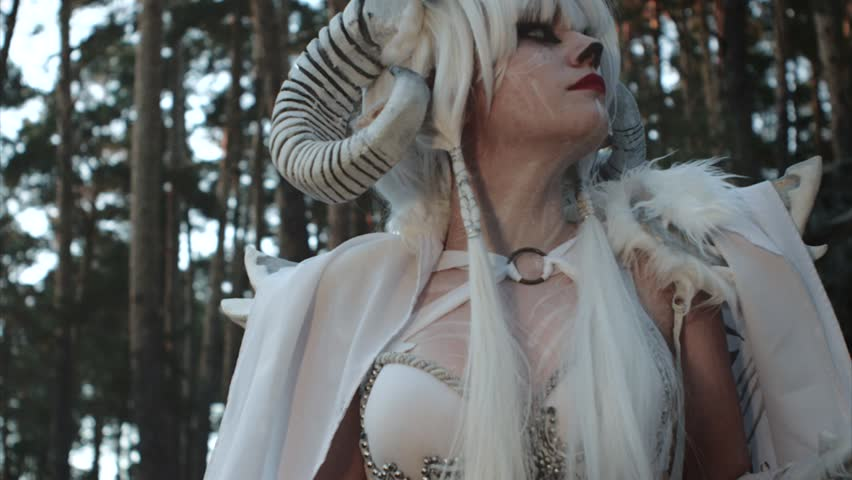 Model dressed like ancient greek faun is posing in woodland. She is having white horns, walleyes and pointed ears, turning head