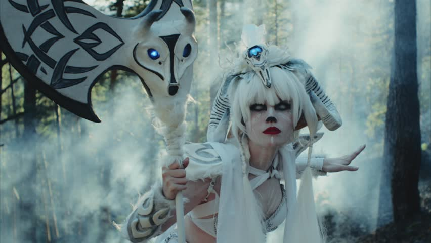 Model dressed like a mythological satyr is posing in a woodland in summer day. She is having horns, long white hair and axe, on her eyes walleyed