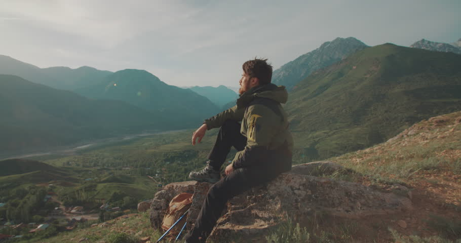 Lonesome climber sitting on top of mountain. Adventurer in expedition. Freedom, zen concept 4k | Shutterstock HD Video #1014323453