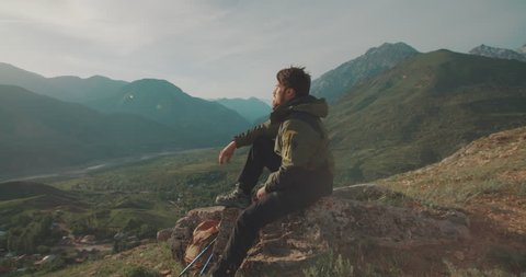 lonesome climber sitting on top of mountain. Adventurer in expedition. Freedom, zen concept 4k