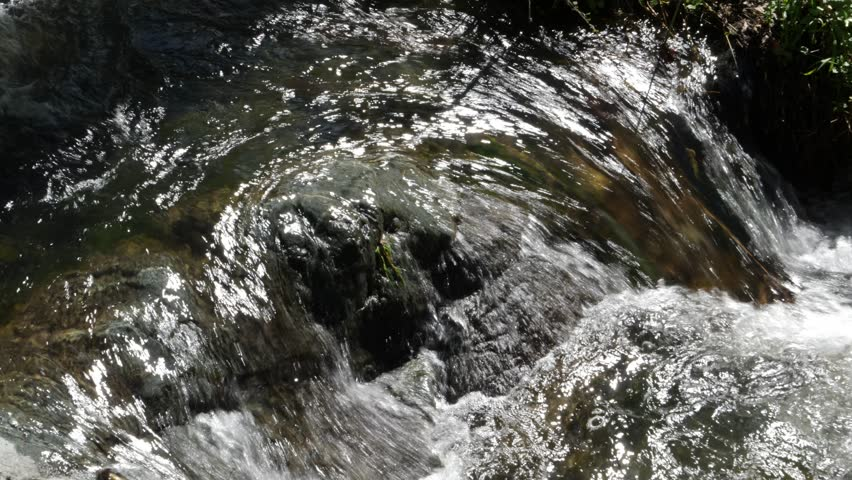 Close up of fresh natural water source flowing fast over rocks
