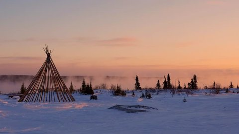 Teepee at dawn by misty northern river in winter, medium