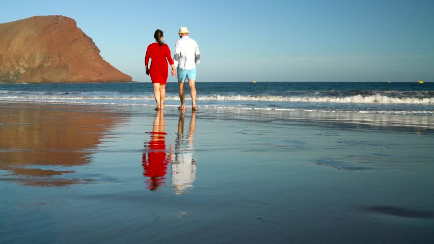 Couple in love carefree walking to the water on the beach. Picturesque ocean coast of Tenerife, Canarian Islands, Spain