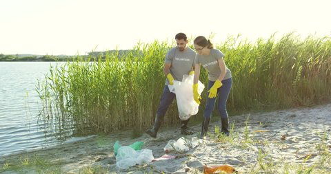 Caucasian couple of volunteers picking up trash and collecting it in the plastic bag while cleaning lake beach.