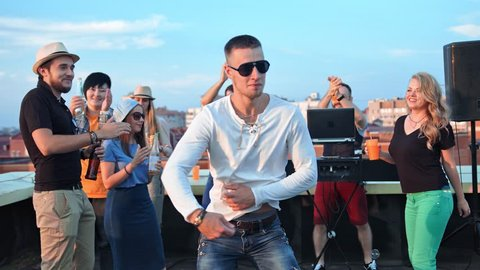 Male hip-hop dancer in sunglasses modern dancing at summer rooftop party