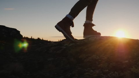 Legs in trekking boots go along the mountain ridge against the backdrop of the rising sun. Travel and adventure concept