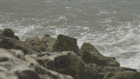Slow motion waves crashing on rocks