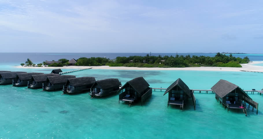 Aerial flying drone view of Maldives white sandy beach on sunny tropical paradise island with aqua blue sky sea water ocean 4k luxury 5 star resort hotel water bungalow hut relaxing holiday