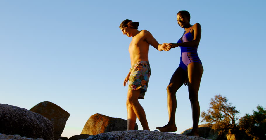 Couple walking hand in hand on the rock at beach 4k | Shutterstock HD Video #1014410153