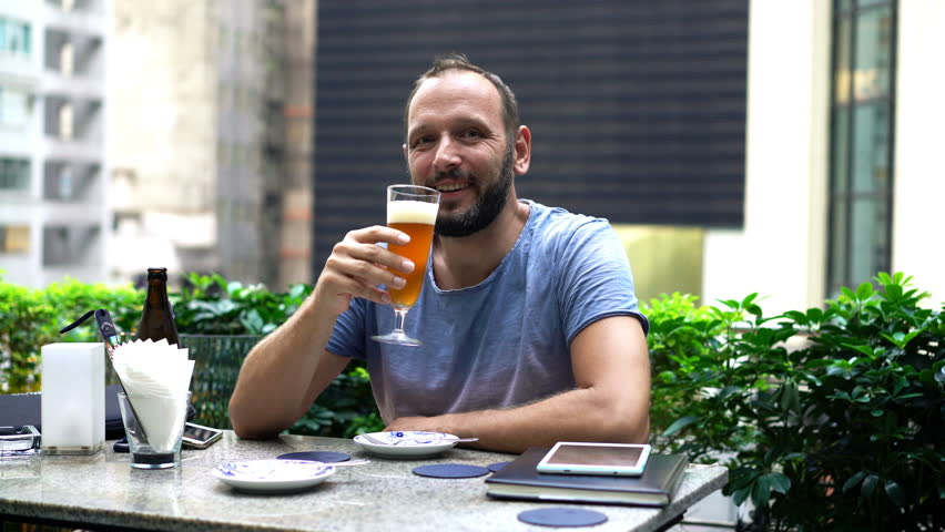 Portrait of happy, young man drinking beer in bar at city  | Shutterstock HD Video #1014448553