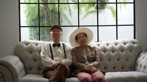 Old Asian couple talking in retro luxury house