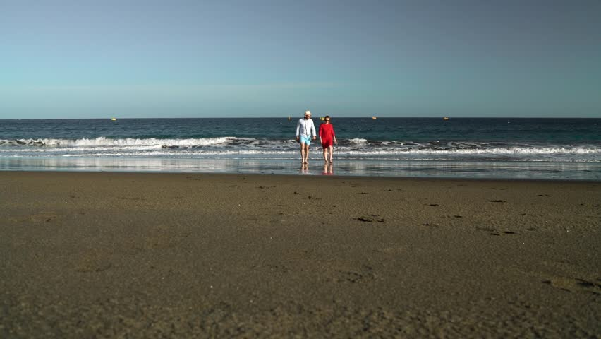 Couple in love carefree walking from the water on the beach. Picturesque ocean coast of Tenerife, Canarian Islands, Spain. Slow motion