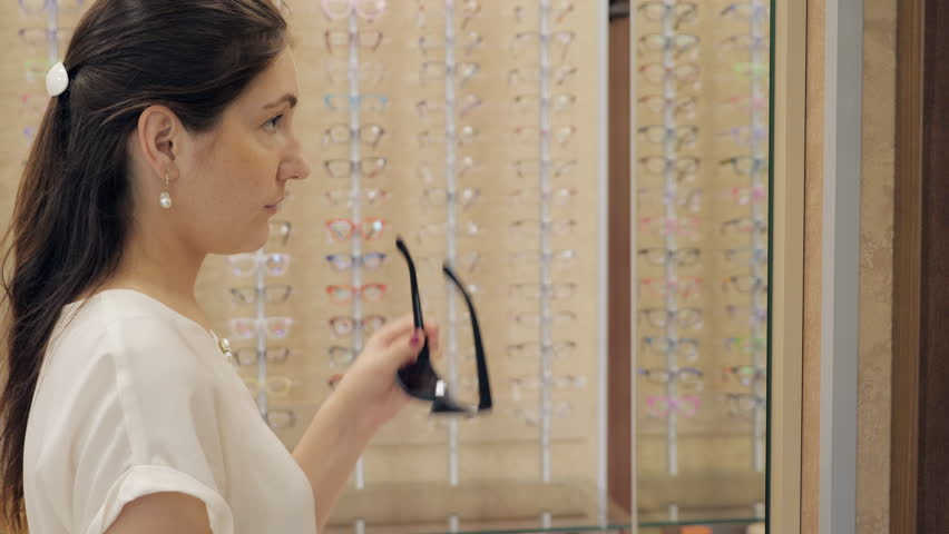 woman in an optician shop trying on sunglasses in front of a mirror.