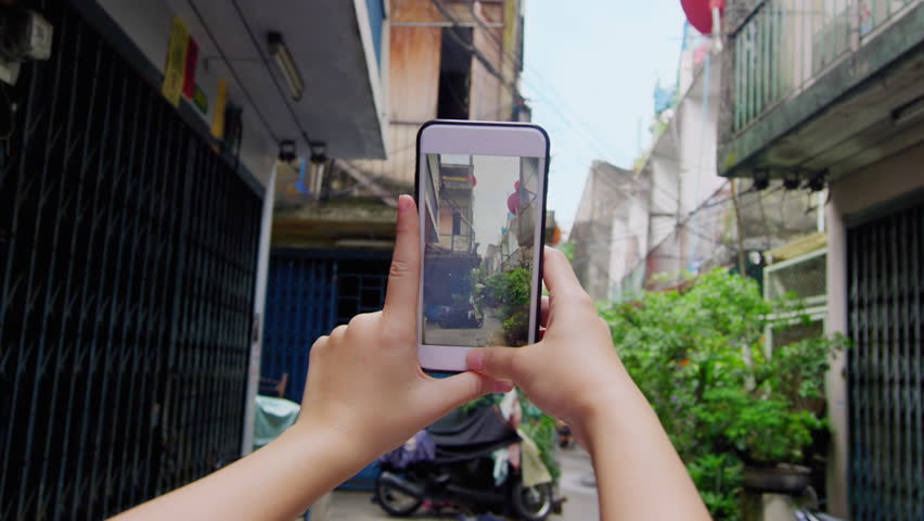 Close up of woman hands taking photo of Bangkok alley way street corner with smartphone in Thailand Asia. Slow motion pov.