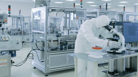Gliding Shot through Sterile High Precision Manufacturing Laboratory where Scientists in Protective Coverall's Use Computers and Microscopes, doing Pharmaceutics, Biotechnology and Semiconductor Resea