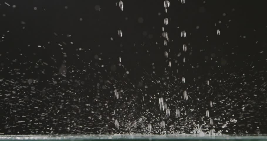 Droplets of water fall from a height on a flat surface. Water droplets and splashes scatter in different directions on a black background. Slow motion. Full HD video, 240fps,1080p