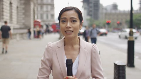 Asian news reporter reporting to camera in the city
