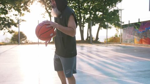 Stylish middle aged man with long gray bearded playing basketball during sunset