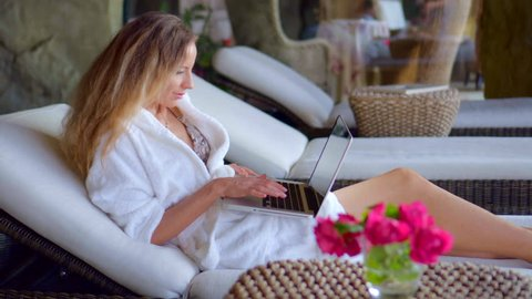 Beautiful Girl Relaxing in the Spa, near swimming pool, Using Laptop on the Vacation. Digital Devices, New Technology