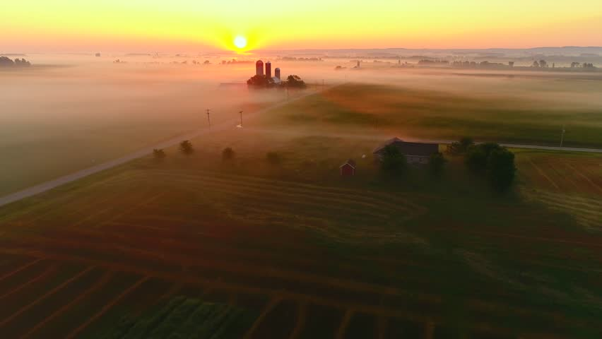 Ethereal fog shrouded rural landscape at sunrise with surreal beauty, aerial view.