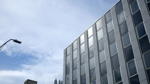 An establishing exterior shot of a chrome gray office building on summer day