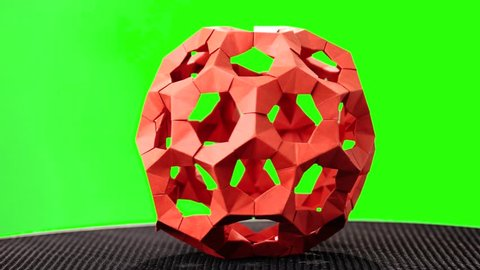 Red rotating modular origami. Green hromakey background for keying.