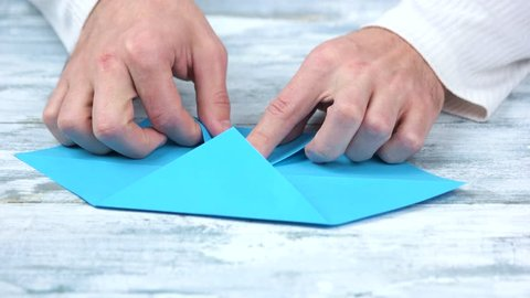 Crafting origami figure with blue paper. Male hands, folding and bending colourful paper sheet.