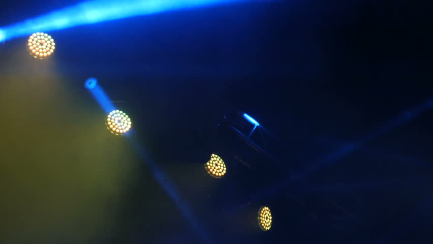 Flashing blue and yellow light in the smoke on the rock concert scene
