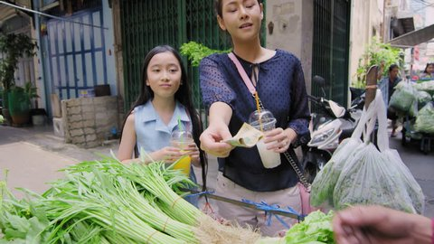 Asian mother and daughter buying traditional Asian street food vegetables from street food vendor Bangkok Thailand Asia. Slow motion.
