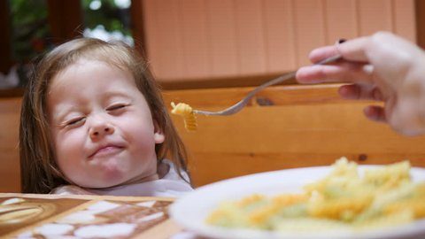 Cute Little Funny Girl Don't Want to Eat Pasta for Lunch. Mother Feeding Daughter with Fork. 4K.