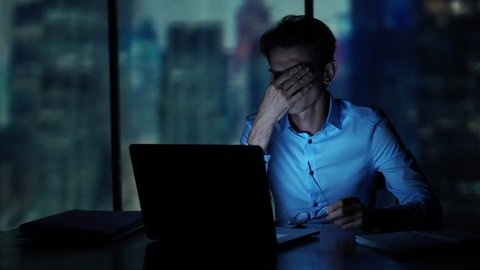 Tired young man working on a laptop late night in the office. Sleepy Businessman sitting at desk in dark office