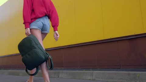 sexy woman with a backpack, walking along the yellow wall in red sweatshirt and short denim shorts. focus on backpack. motion camera