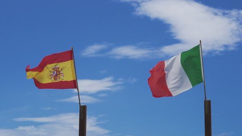 Italian and Spanish flags wave in the wind, in slow motion, against the sky as a background