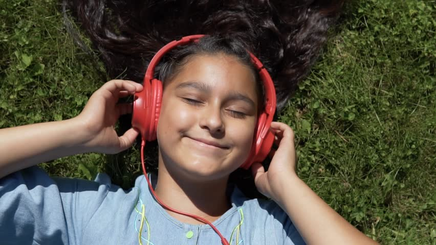 Attractive girl with long black hair lies on the grass in the park and listens to music on the headphones of red color having a good mood.slow motion. | Shutterstock HD Video #1014671873